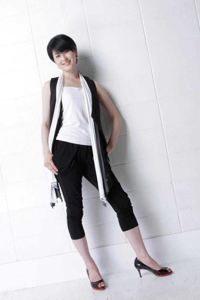 白いシャツに黒いパンツをはいて立っている阿部哲子の画像